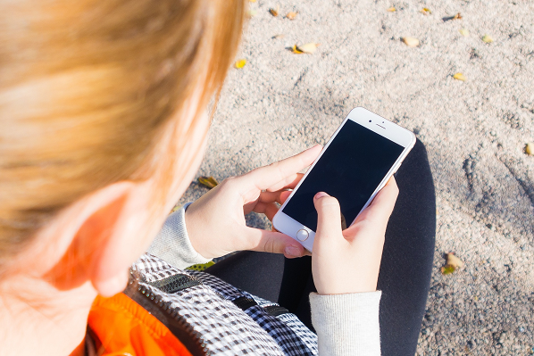 An image of a girl holding a mobile phone device