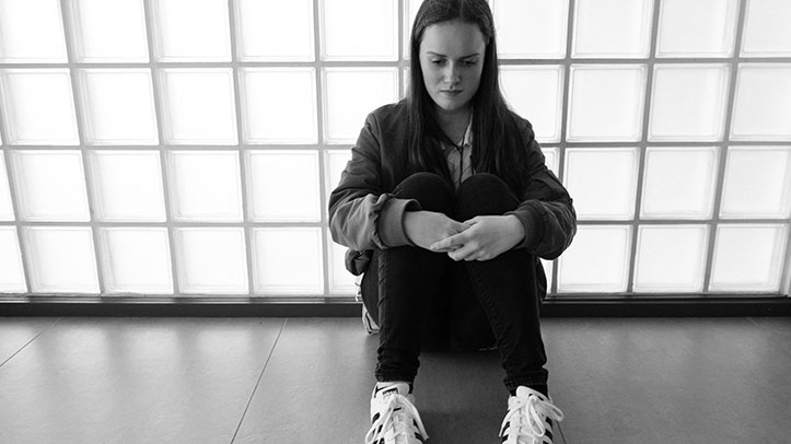 Teenager sitting on floor
